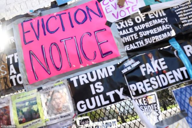 Signs and posters covered a temporary security fence outside the White House with many calling President Donald Trump a 'loser' and demanding he leave the Oval Office
