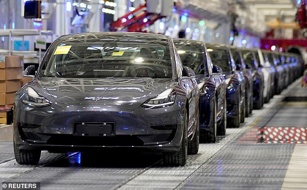 In demand: Tesla Model 3 cars roll down the production line at the electric car maker's factory in Shanghai, China. Scottish Mortgage has almost £2bn tied up in the company
