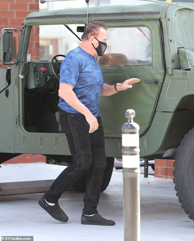 His favorite car:Arnold had on a bright blue camo top and black slacks as he added a black face mask when going to his Hummer car