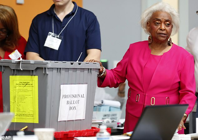 Broward County Supervisor of Elections Brenda Snipes, right, shows a ballot box that was found in a rental car after the elections and turned out to only contain election day supplies, as election employees sort ballots and prepare to count them, Monday, Nov. 12, 2018, in Lauderhill, Fla.