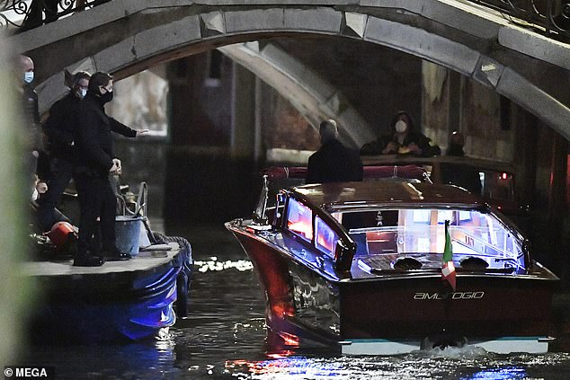 Leap of faith: Tom was seen jumping onto a boat that had been sailing through the Venetian canals