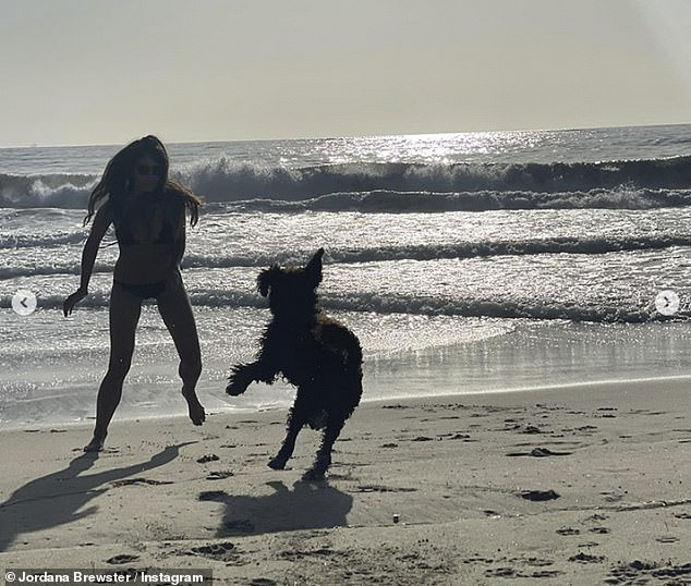 Playful pup: Jordana chased her dog around on the beach as they both looked to be blowing off some steam