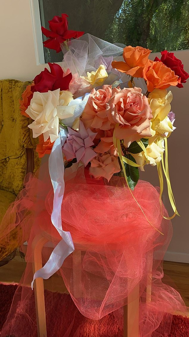 Stunning: Adding a touch of glamour to her arrangements, the mom-to-be placed pink pieces of tulle over a vase filled with red, yellow and orange roses