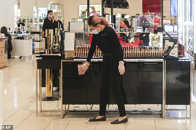 A worker inside a retail department store wipes down a cosmetics display shelf in Melbourne on October 28 (pictured) as shops finally reopened in the city