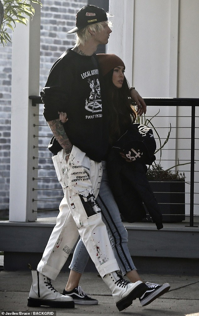 Streetwear chic: She held hands with Kelly, 30, who sported a printed black Local Authority sweatshirt with white printed INDVLST pants and white leather creepers with black soles