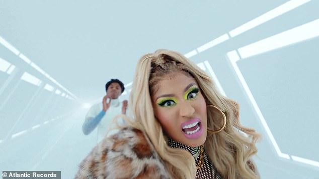 Fancy:Nicki alternated in the video between that outfit and a second one featuring a brown-spotted fur coat, a chainmail top and a blonde wig to frame her gold hoop earrings