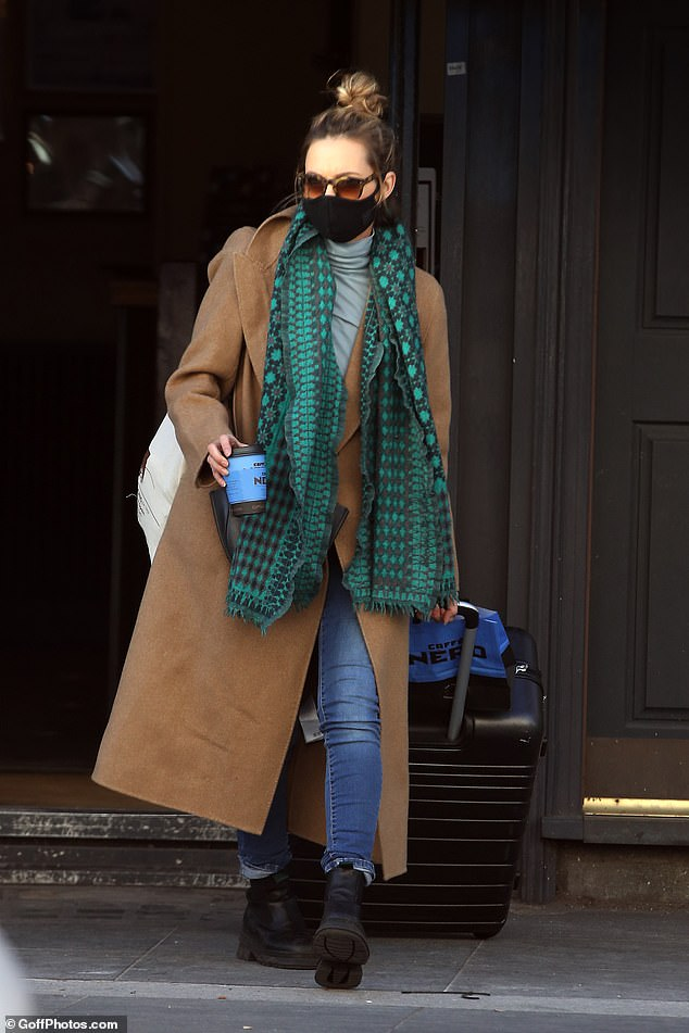 Looking good:Kara cut a stylish figure in her long winter coat, which alongside her scarf, she teamed with a grey roll neck jumper and blue skinny jeans