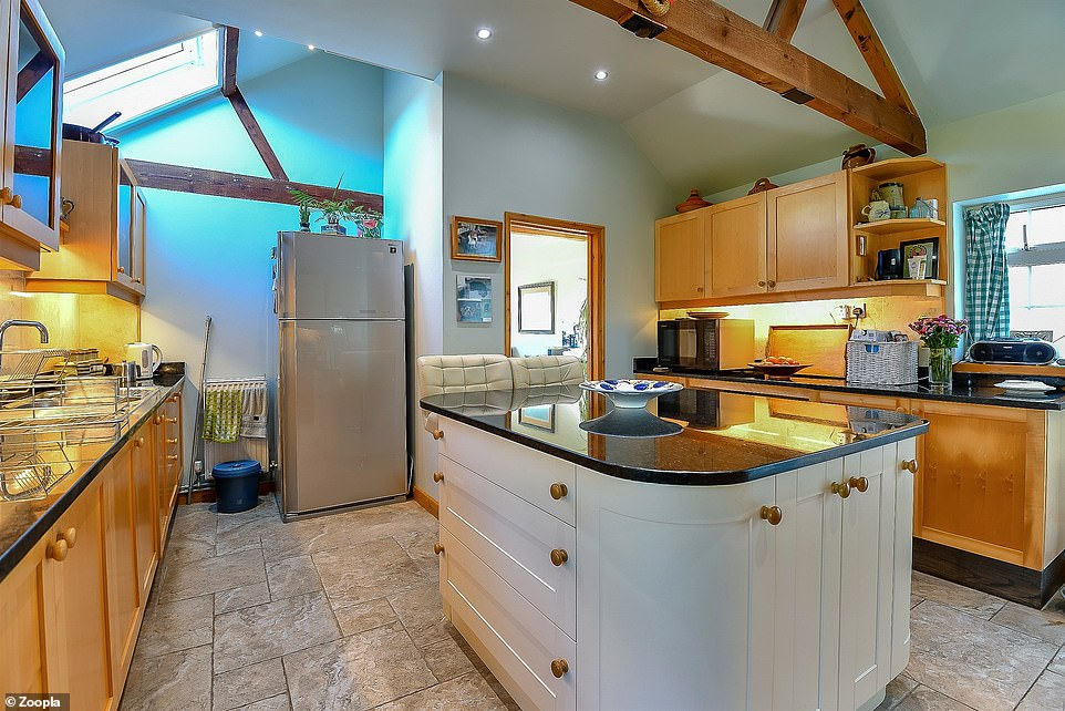 The cottage has a large kitchen with a central island and a vaulted ceiling