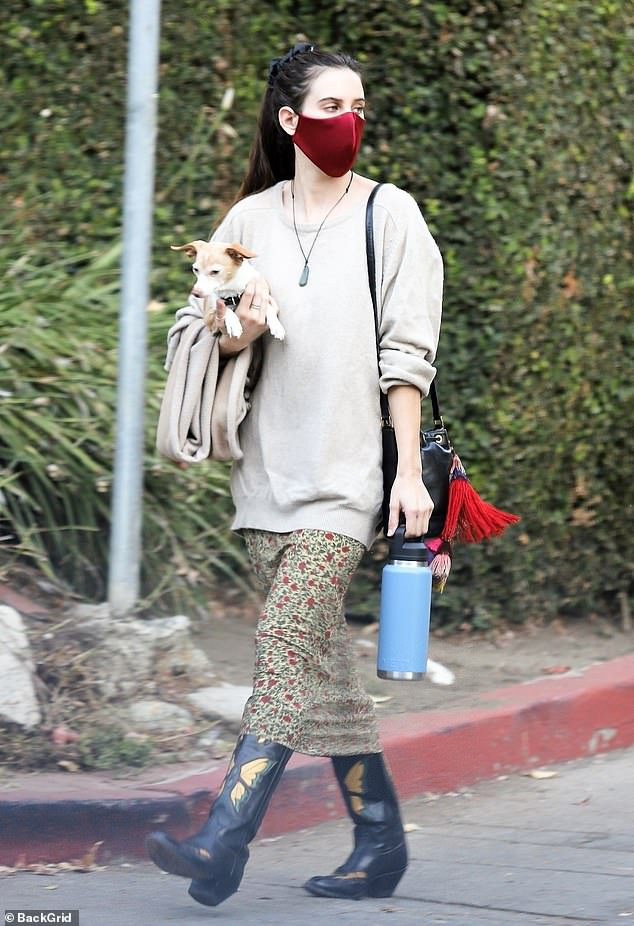 Doting doggie momma: The actress and musician picked up her rescue dog during their walk