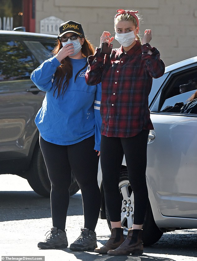 Masked up: Opting to hike with a friend they suited up in masks as she rocked a sporty bandana for the outing