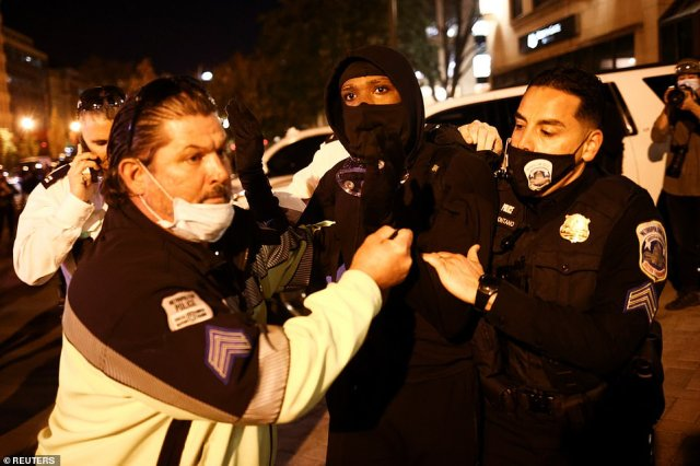 Police officers detain a demonstrator in D.C. on Saturday as anti-Trump protesters and the president's supporters clash