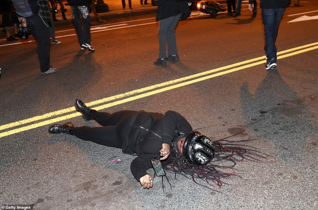 A Black Lives Matter protester bleeds from the mouth as she lays in the middle of the street during a protest following the 'Million MAGA March'. Video shows members of the Proud Boys surrounding her and filming her as she tried to get up before they were pushed back and a police officer came to carry her to the side of the road