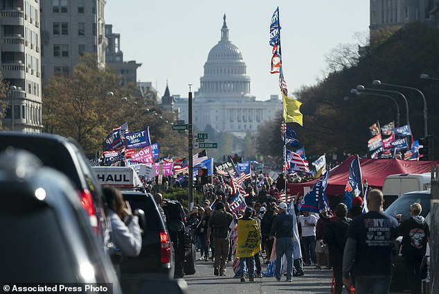 A motorcade carrying President Donald Trump drives by a group of supporters participating in a rally near the White House, Saturday, Nov. 14, 2020, in Washington