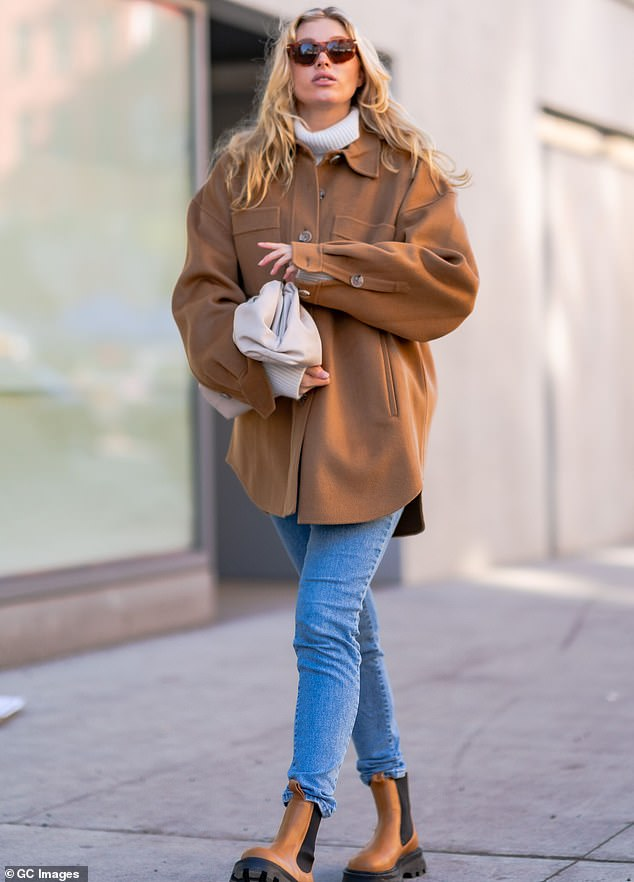 On the move:She pulled on a pair of boots that complemented her jacket and accessorized her ensemble with a white leather handbag