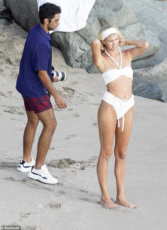 Command attention: Devon Windsor showcased her slender frame in a stunning white bikini for a beach day with her husband Johnny Barbara in St Barts on Saturday