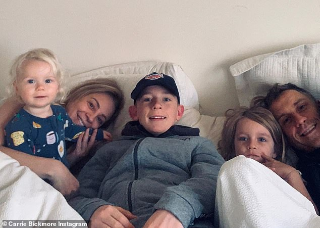 Doting mother:Carrie shares daughters Evie, five, and Adelaide, one, with partner Chris Walker. She also has a son Oliver, 13, from her marriage to Greg Lange, who died after a lengthy battle with brain cancer in December 2010
