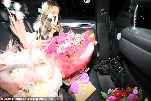 Welcome gits: Luba was seen with a collection of flower bouquets in her car