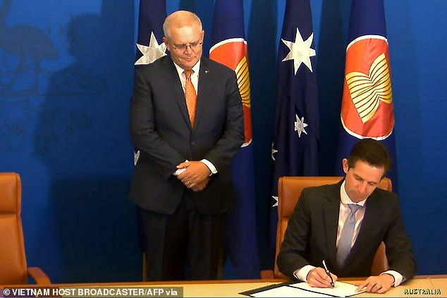 Australia's Prime Minister Scott Morrison (C) watching as Australia's Minister for Trade, Tourism and Investment Simon Birmingham signs the agreement