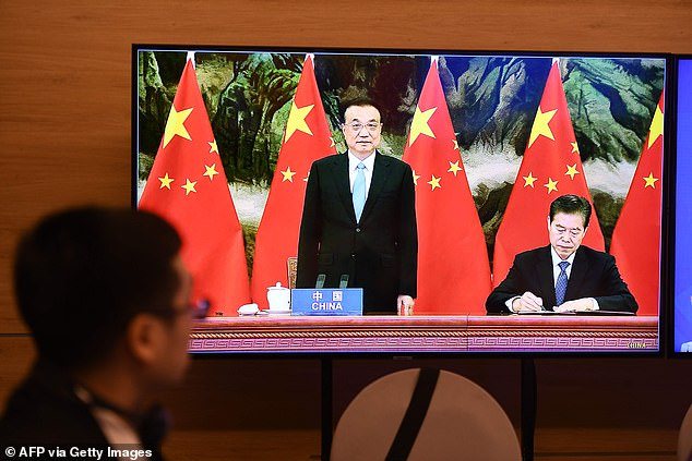 China's Premier Li Keqiang (C) looks on as Chinese Minister of Commerce Zhong Shan (R) signs the agreement