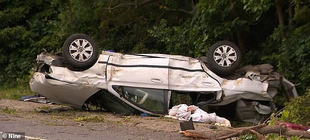 The car left the road in the horrific crash and came to a stop upside down on the road side (pictured)