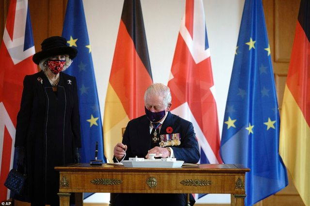 Prince Charles and his wife Camilla sign the guest book before a conversation at Bellevue Palace in Berlin this morning
