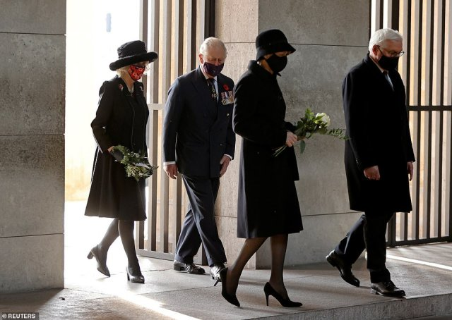 Camilla, Duchess of Cornwall, and First Lady of Germany, Elke Buedenbender, arrive carrying small bunches of flowers to lay alongside the wreaths. Pictured with President Frank-Walter Steinmeier and Prince Charles