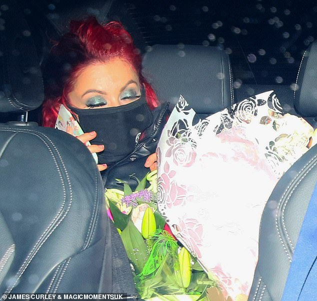 Phone call: Dianne was on the phone as she sat under the large bunch of flowers in the car while her eye shadow looked immaculate following their performance