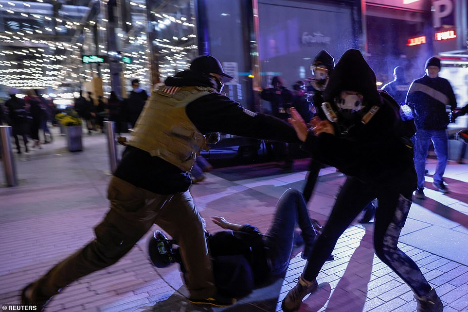 A member of far-right militia Proud Boys clashes with an anti-facist protester as violence continues in D.C.
