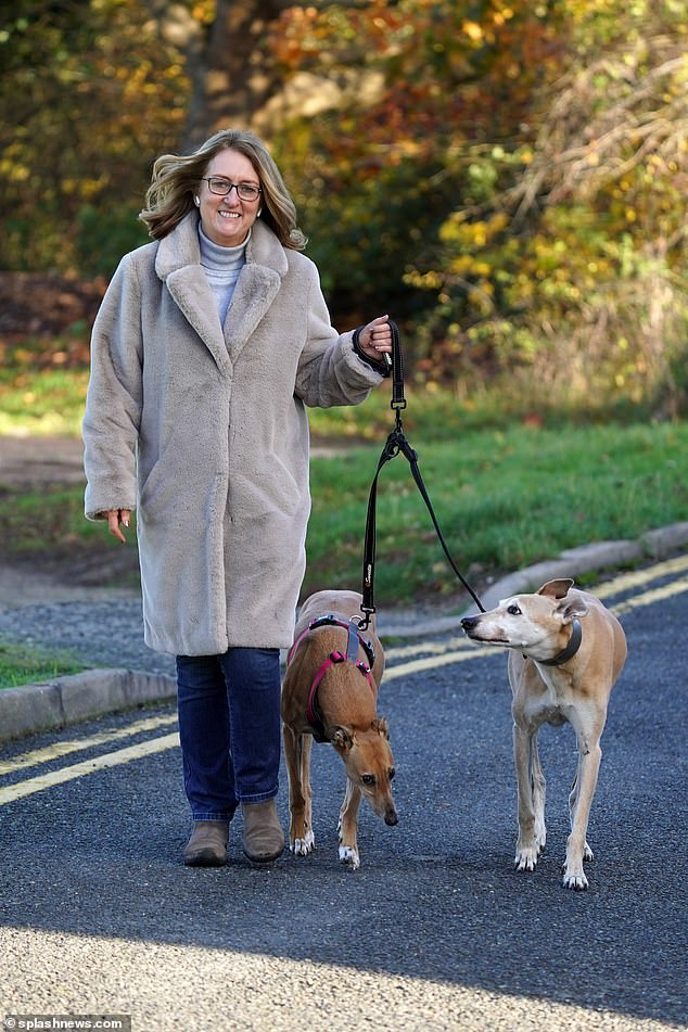 In good spirits: Jacqui Smith still managed to flash a smile after her Strictly axe as she enjoyed a walk with her dogs in Malvern on Saturday morning