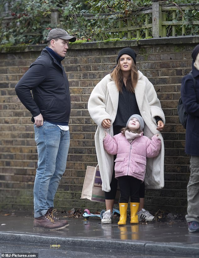 Adorable:The former Made In Chelsea star, 30, cut a chic figure in a cream fleecy coat as adorable India sheltered under the outfit during a rainy walk
