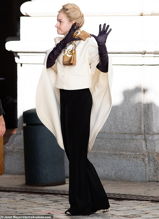 In character:The blonde beauty was elegantly dressed in a white caped jacket paired with a flowing set of black slacks; she accessorized with long leather gloves and a printed scarf while keeping her normally flowing blonde hair in a tight bun