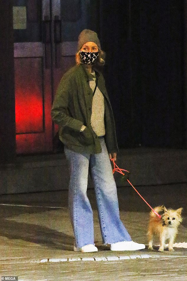 Naomi Watts dresses down in a grey beanie as she walks her rescue dog Izzy