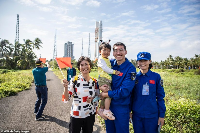 Staff members celebrate after the rocket, carrying China's new lunar probe Chang'e-5 on top, was moved to the launch area
