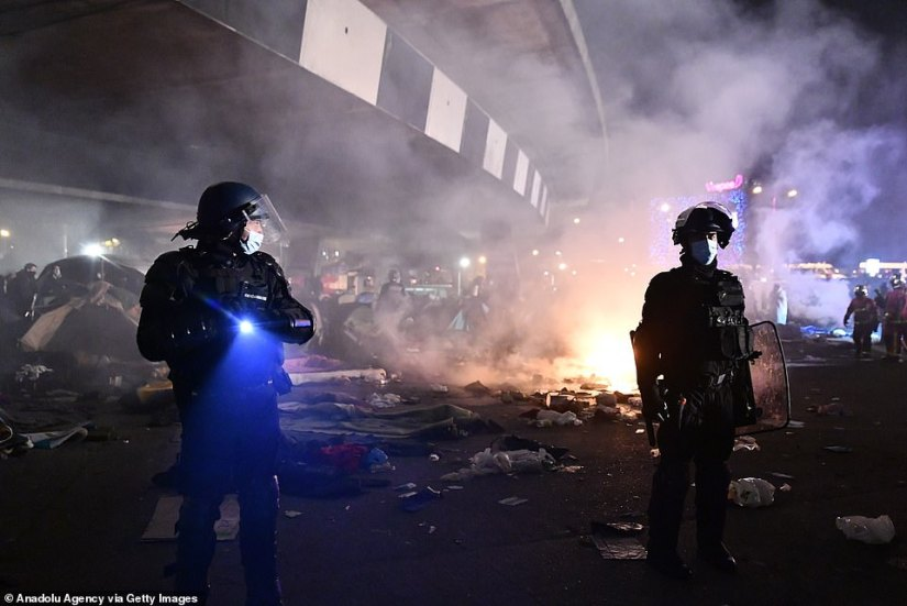 Police officers in riot gear stand guard last night