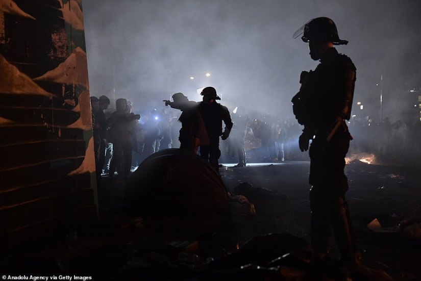 French riot police deal with unruly migrants last night during the evacuation of the colossal camp on the outskirts of Paris