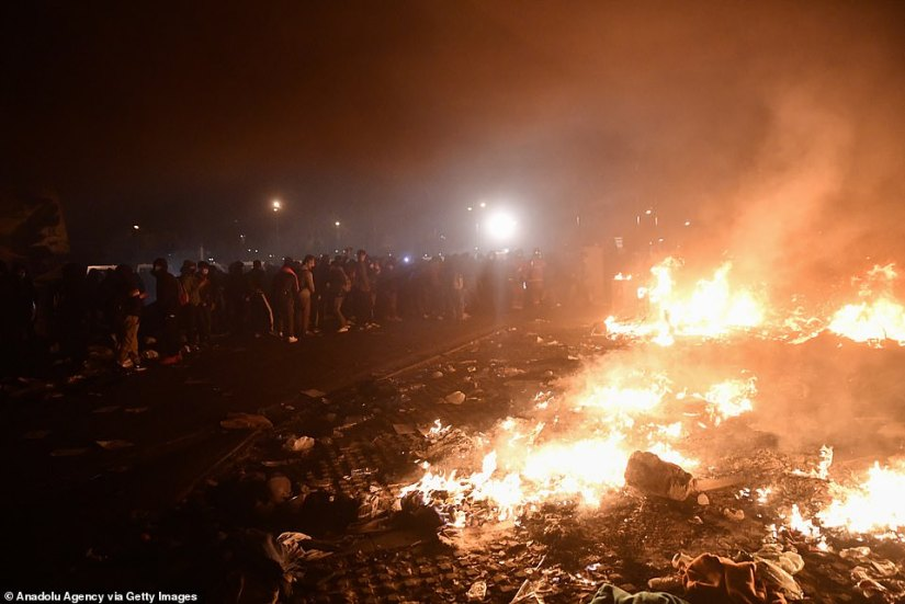 The burning remains of the migrant camp are watched by the former residents