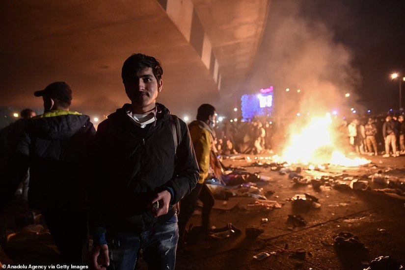 A migrant stands with his back to a raging inferno close to the Stade de France stadium on the outskirts of Paris last night