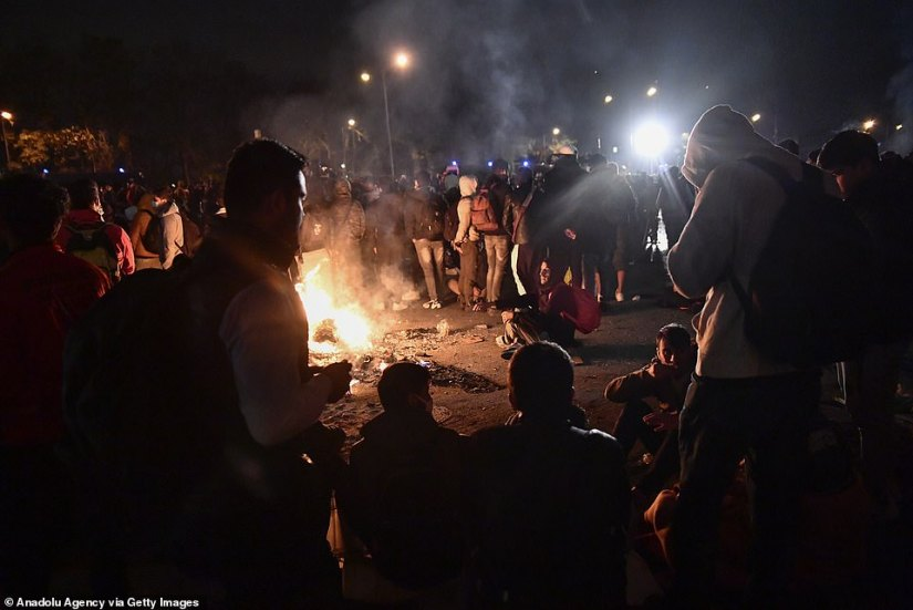 The migrants wait to be moved on beside a bonfire
