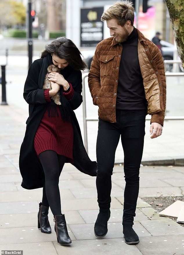 Furry friend: Dancing On Ice's Faye Brookes held her sweet Pomeranian puppy, Bear, during a stroll around Manchester with her boyfriend Joe Davies on Tuesday
