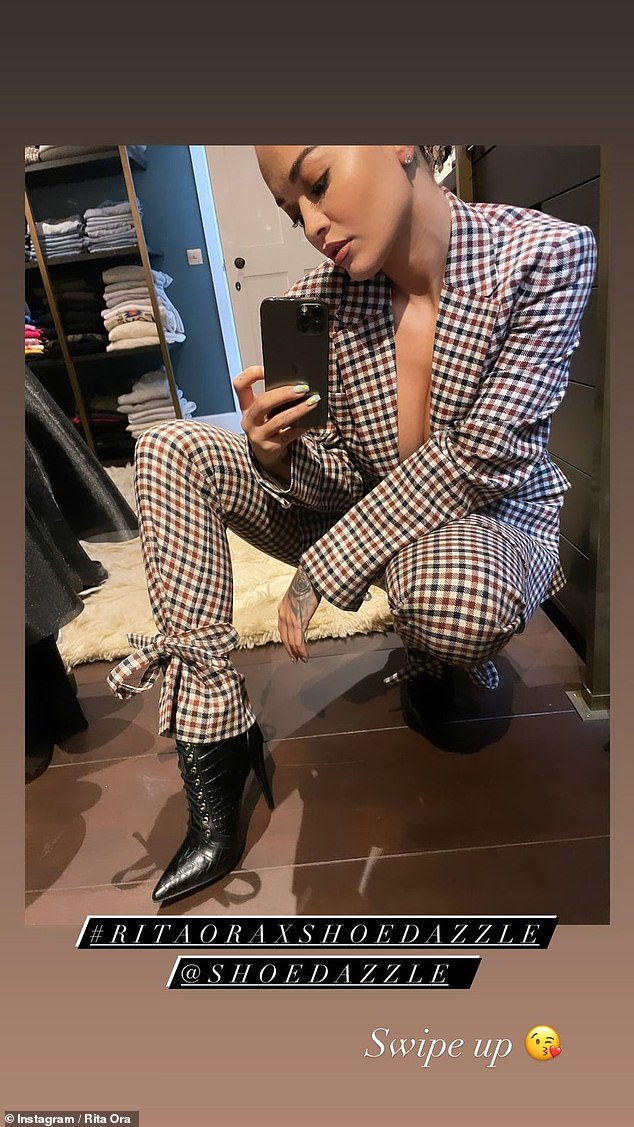 In her element: Living up to her style maven status, the Anywhere hitmaker went braless underneath a checked suit as she posed up a storm in her walk-in wardrobe