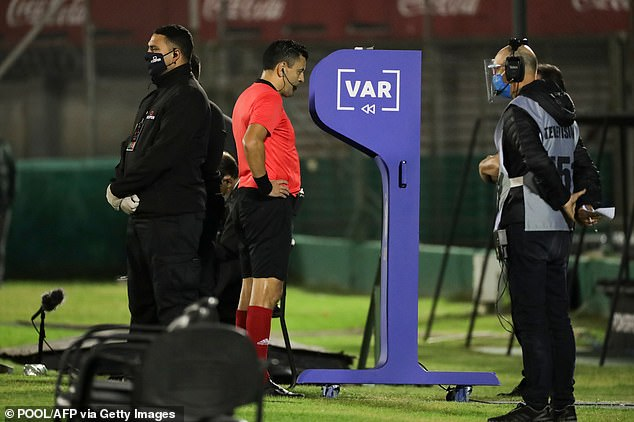 The referee checks his pitchside monitor before upgrading Cavani's yellow to a red card