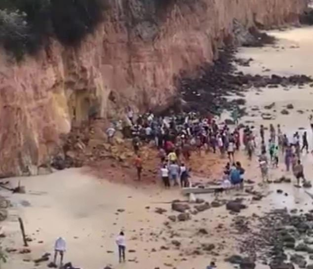 Members of the public gather around the rubble pile on Pipa Beach on Tuesday after the family were buried under the falling rock