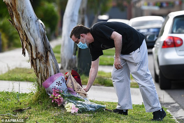 A grief-stricken man is pictured laying flowers outside the home of Ms Manno