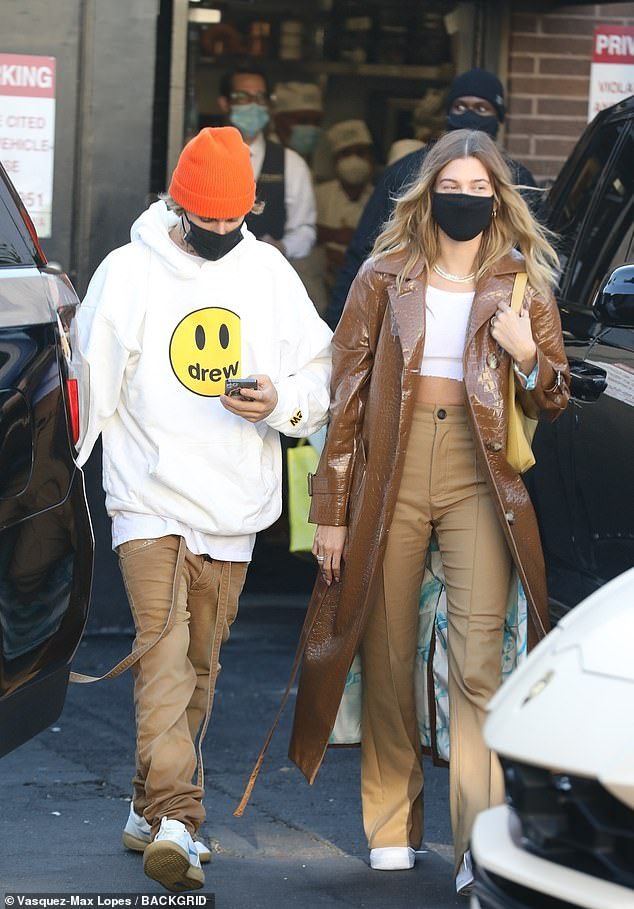 Fall fashions:Justin was his ever-casual self in a huge oversized white hoodie sweatshirt, while Hailey dressed up in abrown patent leather alligator skin trench coat