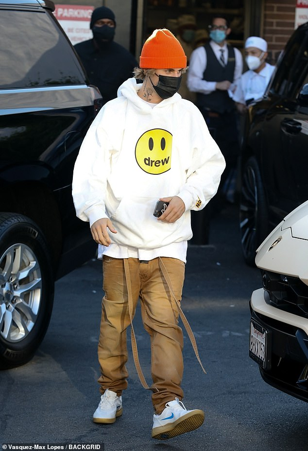 Rounding out his look:On top, Biebs wore a knit orange beanie cap, and on the bottom, he sported white Nike sneakers with a simple blue swoosh