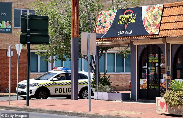 Police are seen patrolling outside the Woodville Pizza Bar in Adelaide on Friday afternoon after it came to light an infected employee lied to contact tracers