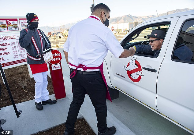 Colorado Springs In-N-Out manager Saul Arreola (in white) shakes hands with Ken Vizzini (right), the first person to get served at the location after waiting on line since Tuesday