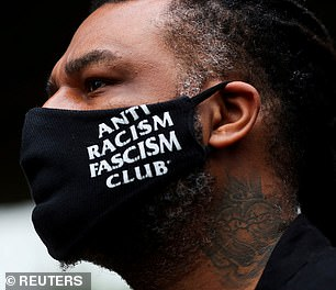 "A demonstrator wears a face mask reading ""Anti racism fascism club"" as he takes part in a march in Sao Paulo"