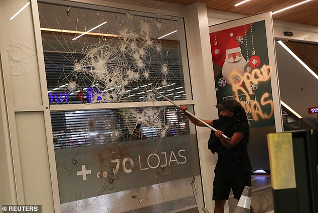 A demonstrator damages glass at a shopping mall during a march in Sao Paulo on National Black Consciousness Day and in protest against the death of Joao Alberto Silveira Freitas