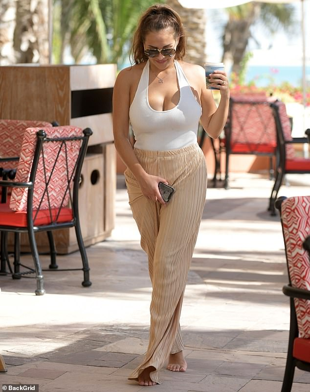 Caffeine boost: Chloe Goodman displayed her ample assets in a white halterneck top as she picked up a coffee before meeting her older sister Lauryn at theImperial Club spa on Friday